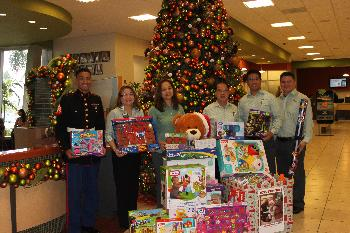 Coast360 executive team with US Marine Sgt. Moses pose alongside toys collected at our Maite HQ